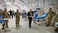 Image of soldiers and businessman in suit walking through an emergency shelter lined with beds and medical equipment