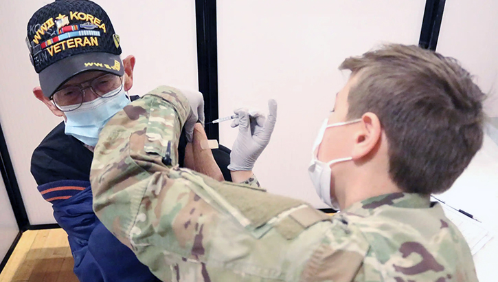 Military personnel wearing a mask, giving the COVID-19 vaccine to a veteran wearing a mask