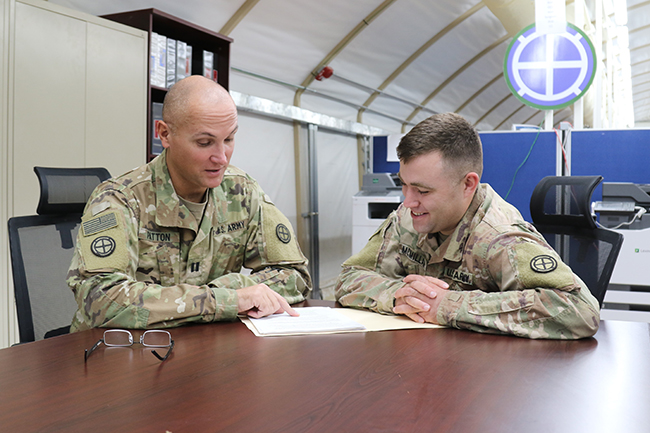 Army Staff Sgt. Michael McMillan (right), 35th Infantry Division behavioral health noncommissioned officer in charge, confers with Army Capt. Trever Patton, 35th ID psychologist, in Kuwait. Embedded behavioral health teams are a key part of providing easy access to care for service members. (Army photo by Staff Sgt. Tina Villalobos)
