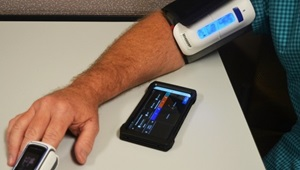 Man's arm with blood pressure cuff and fingertip pulse oximeter