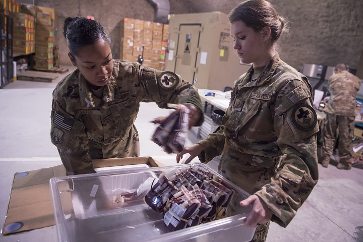 Air Force Staff Sgts. Jasmine Gates, left, and Alexis Ellingson, right, both 379th Expeditionary Aeromedical Evacuation Squadron aeromedical evacuation technicians, inventory and store a shipment of blood in the Blood Transshipment Center (BTC) at Al Udeid Air Base, Qatar. Ellingson and Gates volunteered to prepare blood products for transport at the BTC. The BTC is comprised of a four-person team that orchestrates the flow of blood and platelet products to 72 forward operating locations and eight mobile field surgical teams throughout U.S. Central Command's area of responsibility. (U.S. Air Force by Tech. Sgt. Christopher Hubenthal)