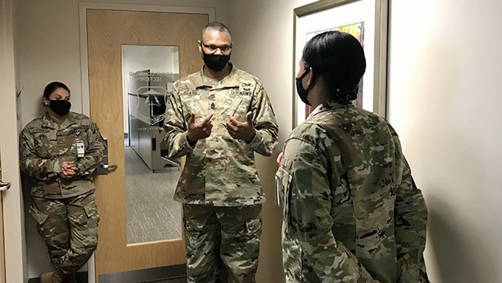 Three military personnel, wearing masks, having a discussion in a room