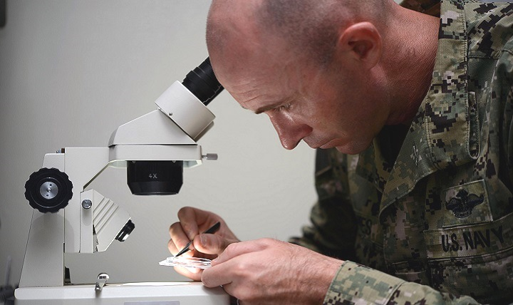 Navy Petty Officer 1st Class James Bowes, Camp Lemonnier's expeditionary medical facility senior preventive-medicine technician, places mosquitoes on a dish to view under a microscope at Camp Lemonnier, Djibouti. Bowes, a member of the camp's mosquito-control program, routinely analyzes mosquitoes to help determine the risk of mosquito-borne diseases like malaria. (U.S. Navy photo by Petty Officer 1st Class Tom Ouellette)