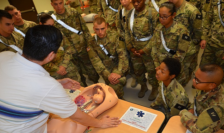 "Alonzo Gonzales, a Combat Medic Program emergency medical technician course instructor, lectures students in Alpha Class 70-17 about different obstetrics complications  utilizing a specialized OB training manikin. The OB manikins resemble life-size pelvic cavities inside which the ""fetus"" can be positioned to replicate any number of complicated situations. (U.S. Army photo by Lisa Braun)"