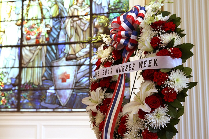 The MHS wreath presented at the beginning of National Nurses Week at the 3rd annual wreath laying ceremony stands against the stained-glass backdrop of Tiffany Circle Hall at the American Red Cross headquarters, Washington, D.C. (MHS photo)