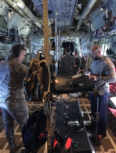 Dr. David Burch (right), a research biomedical engineer and the medical technology solutions team lead for En Route Care Medical Technology Solutions Research Group with the 711th Human Performance Wing at Wright-Patterson Air Force Base, Ohio, collects data on vibration profiles while flying aboard a C-130J Super Hercules. (Courtesy photo)