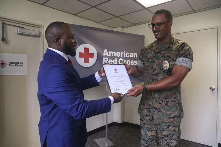 American Red Cross Services to the Armed Forces regional program manager Don Gardner awards Marine Staff Sgt. Jonathan McClure with the American Red Cross Presidential Certificate of Merit in Okinawa, Japan, April 23, 2019. (U.S. Marine Corps photo by Lance Cpl. Savannah Mesimer)