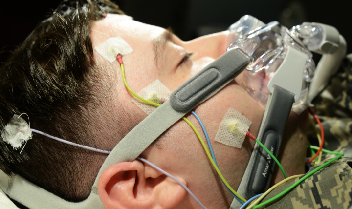 An Airman is hooked up to wires and a continuous positive air pressure mask in the 673d Medical Group Sleep Disorder Clinic at the Joint Base Elmendorf-Richardson Hospital, Alaska. The equipment monitors a patient's brain function, heart rate, temperature, breath, and movement. (U.S. Air Force photo by Airman 1st Class Christopher R. Morales)