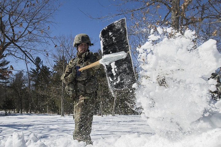 Army Sgt. 1st Class Joseph Seifridsberger shovels knee-deep snow to build a simulated