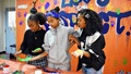 "Midori Robinson, Kyleigh Rose and Keisha McNeill paint their hands so they can put a handprint on the ""Love is Respect"" mural during the Camp Zama Youth Center Teen Dating Violence Awareness Lock-In at Camp Zama. (U.S. Army photo by Winifred Brown)"