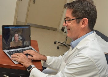 A MHS health care provider holds a virtual health visit with a patient.