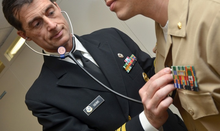 Navy Capt. Jesse Geibe, Naval Hospital Jacksonville director for public health, listens to a patient's heart rate. The Jacksonville Business Journal honored Geibe as a 2016 Health Care Hero. Defense Department officials are reminding military and civilian employees that they must report their health care coverage to the Internal Revenue Service when they file their 2016 federal income tax form. (U.S. Navy photo by Jacob Sippel)
