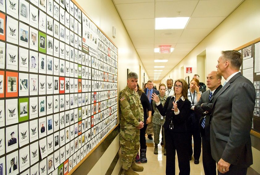 Todd Weiler, Assistant Secretary of Defense for Manpower and Reserve Affairs, and Ronald Keohane, Deputy Assistant Secretary of Defense for Military Community and Family Policy; listen to Deborah Skillman, Director, Casualty, Mortuary Affairs and Military Funeral Honors from the Office of the Deputy Assistant Secretary of Defense for Military Community and Family Policy, explain the display board of confirmed USS Oklahoma remains identified by the Armed Forces DNA Identification Laboratory Nov. 4, 2016, at Armed Forces Medical Examiner System on Dover Air Force Base, Del. Weiler and Keohane received briefings and met with personnel at the Air Force Mortuary Affairs Operations, AFMES and the Joint Personal Effects Depot. (U.S. Air Force photo by Roland Balik)