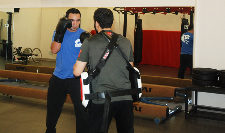 Volunteer boxing coach Mike Martin (right) shows boxing technique to Daniel Irwin, Jr. (Courtesy photo)