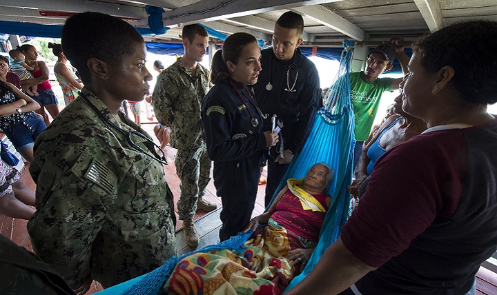 U.S. Navy Lt. Cmdr. Nehkonti Adams, an infectious diseases specialist, left, and U.S. Navy Lt. Gregory Condos, an internal medicine specialist, middle, work with 2nd Lt. Raissa Vieira Sanchez, a Brazilian medical officer, right, to diagnose an elderly woman on her houseboat near a remote village along the Amazon River in Brazil. (U.S. Navy photo by Mass Communication Specialist 2nd Class Andrew Brame)