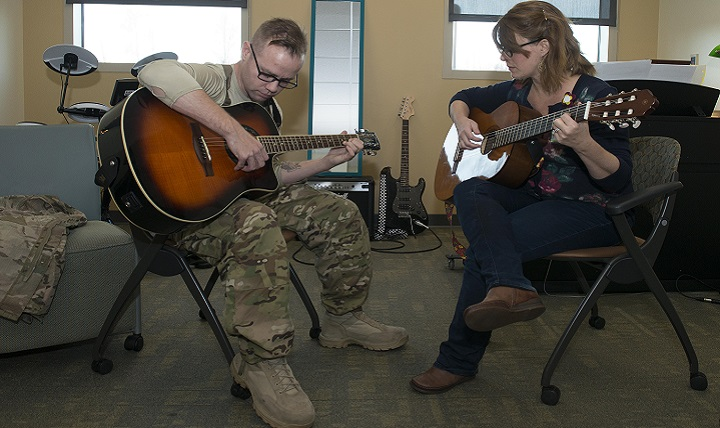 Army Staff Sgt. Sean Young, 2nd Battalion, 377th Parachute Field Artillery Regiment training room noncommissioned officer, strums the guitar during music therapy with Danielle Kalseth, 673rd Medical Operations Squadron creative arts and music therapist, at Joint Base Elmendorf-Richardson, Alaska. Music therapy sessions help rehabilitate patients with traumatic brain injury. (U.S. Air Force photo by Airman 1st Class Caitlin Russell)