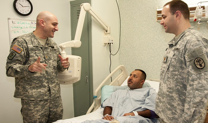 Army Maj. Michael Goldberg (left), chief, Gastroenterology, William Beaumont Army Medical Center, and Army Maj. Christopher Calcagno (right), gastroenterologist, WBAMC, speak to Army Staff Sgt. Mario Talavera (center), following the first incisionless fundoplication procedure to treat gastroesophageal reflux disease (GERD) performed in the Department of Defense, at WBAMC. (U.S. Army photo by Marcy Sanchez)