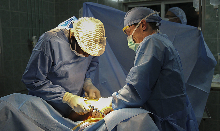 Dr. Mansour Niang (left), a Senegalese gynecologist, and Dr. Anthony Donaldson, a major in the Vermont Air National Guard, perform surgery during a joint medical readiness training exercise at a hospital in Dakar, Senegal. (U.S. Army photo by Maj. Simon Flake)