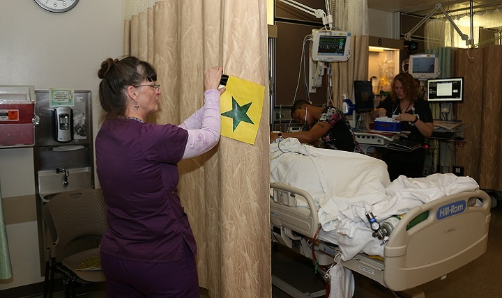 Registered nurse Sheila Carroll hangs a green star on the curtain to signify that this patient may wake up after surgery with Emergence Delirium.