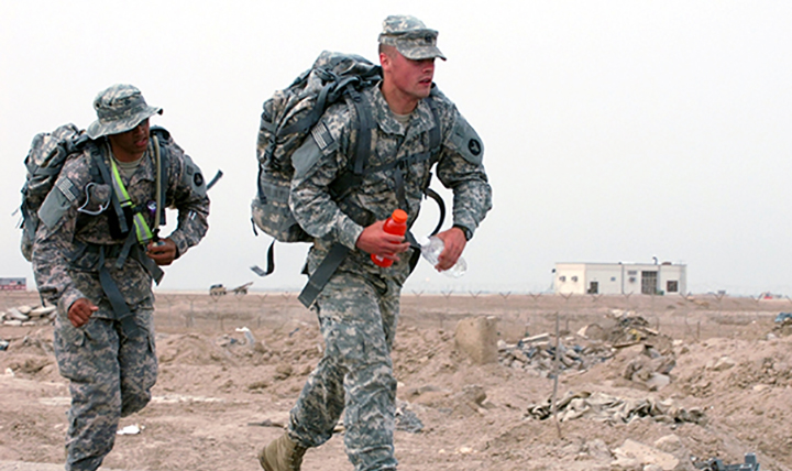 Two U.S. service members perform duties in warm weather where they may be exposed to extreme heat conditions and a higher risk of heat illness.