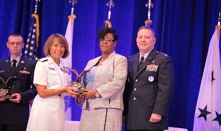 Vice Admiral Raquel C. Bono, director of the Defense Health Agency, presents the DHA/J-6 Category II Civilian of the Year Award to Ms. Cynthia Amires at the Defense Health Information Technology Symposium on July 25, 2017 in Orlando, Florida.