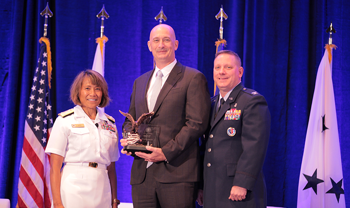 Vice Admiral Raquel C. Bono, director of the Defense Health Agency, presents the DHA/J-6 Field Grade Officer of the Year Award to Lieutenant Colonel (Ret.) Mark Mellott at the Defense Health Information Technology Symposium on July 25, 2017 in Orlando, Florida.