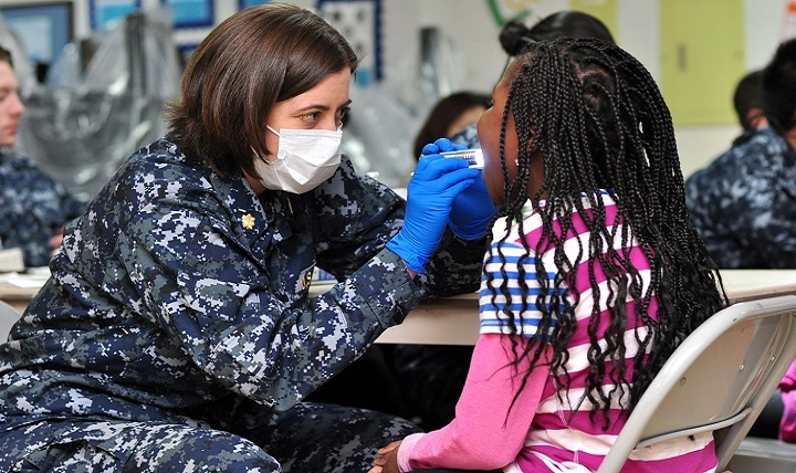 Navy Lt. Cmdr Carey Collins, a dentist assigned to U.S. Naval Hospital, Yokosuka, Japan, conducts a basic dental screening on a child.