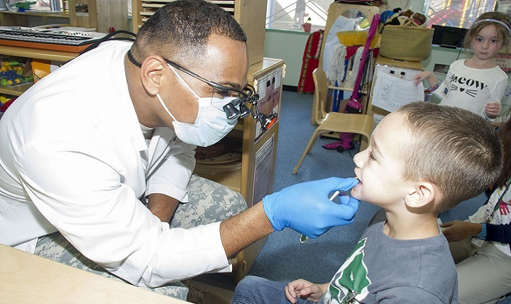 Army Maj. Demarcio Reed, commander of U.S. Army Dental Activity-Japan, conducts a dental screening of Xavier Pittman, 5, in the Strong Beginnings Class at the Sagamihara Family Housing Area's Child Development Center.