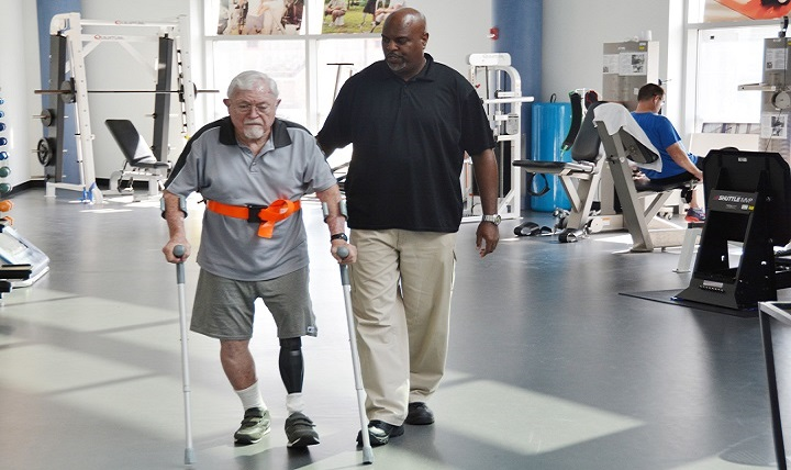Physical therapy technician Troy Hopkins assists retired Maj. Gen. William L. Moore Jr. at the Center for the Intrepid, Brooke Army Medical Center's outpatient rehabilitation facility on Joint Base San Antonio-Fort Sam Houston in San Antonio.