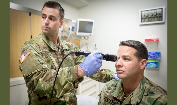 In a demonstration of the telehealth process at Fort Campbell's Blanchfield Army Community Hospital, clinical staff nurse Army Lt. Maxx Mamula examines mock patient Army Master Sgt. Jason Alexander using a digital external ocular camera. The image is immediately available to a provider at Fort Gordon's Eisenhower Medical Center, offering remote consultation. (U.S. Army photo by David E. Gillespie)
