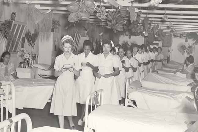 Navy nurse leading Chamorro student nurses in ward inspection (1948). The Navy became involved in the affairs on Guam in 1898. In 1911, Navy nurses established a training school in Guam to instruct Chamorro women in health and hygiene. (BUMED archives)