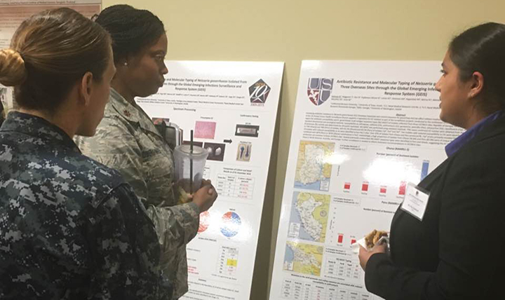 Nazia Rahman, right, manager of the Uniformed Services University's Neisseria gonorrhoeae (GC) Repository, discusses a poster on the sexually-transmitted infection with U.S. Air Force Major Trinette Flowers-Torres, lead for GEIS's Antimicrobial Resistance (AMR) Focus Area, left, and Navy Commander Franca Jones, front, chief of GEIS, examine poster on AMR surveillance. (AFHSB photo by Briana Booker).