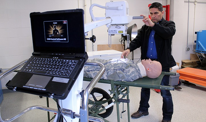 U.S. Army Medical Materiel Agency Equipment Specialist Diego Gomez-Morales demonstrates the new Portable Digital Radiography System that will replace two aging devices, including an X-ray generator and an accompanying computerized reader system. The PDRS combines these capabilities into a single lightweight X-ray unit intended for use by deployed medical, Special Operations and Mortuary Affair Army units. (U.S. Army photo by Ellen Crown)