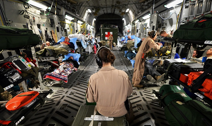 Members of the of the 455th Expeditionary Aeromedical Evacuation Squadron assist patients on medical transport flight