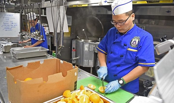 Navy Culinary Specialist Seaman Peng Yan, from Los Angeles, prepares oranges in the galley aboard the guided-missile destroyer USS Stockdale.