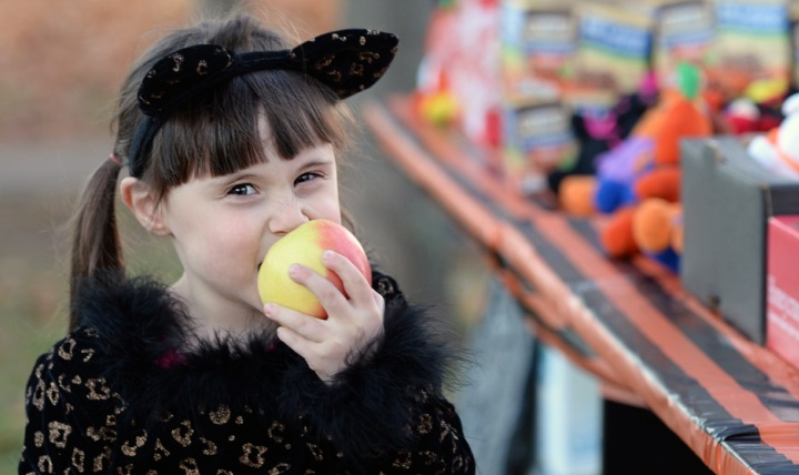 A child eats an apple during a Trunk-or-Treat event, which featured a healthy snack station as an alternative to candy, at Ramstein Air Base, Germany. (U.S. Air Force photo by Senior Airman Jimmie D. Pike)