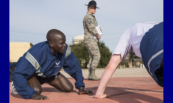 Air Force Airman 1st Class Guor Maker, now a dental assistant currently in technical training, supports an Airman taking a physical fitness test. Maker was selected as a physical training leader for his time at Basic Military Training, his duties include leading the flight during warm-ups and providing support for struggling trainees. (U.S. Air Force photo by Airman 1st Class Dillon Parker)
