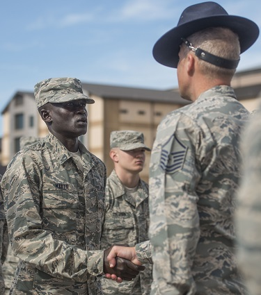 """Guor Maker, then a trainee at basic military training, receives an """"Airman's Coin"""" at the Coin Ceremony Feb. 1, 2018 outside the Pfingston Reception Center at Joint Base San Antonio-Lackland, Texas. Maker was recognized by his wingmen as a selfless leader and motivator during his time at BMT. (U.S. Air Force photo by Airman 1st Class Dillon Parker)"""
