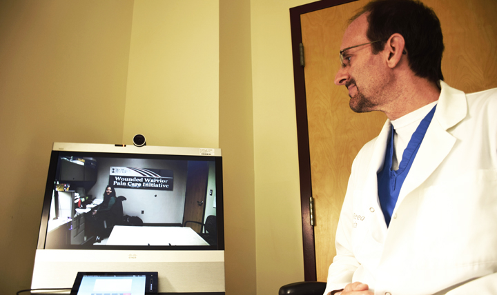 Dr. Christopher Spevak, director of the opioid safety program for the National Capital Region in and around Washington, D.C., uses the telehealth equipment at Walter Reed National Military Medical Center, Bethesda, Maryland. (DoD photo by Kalila Fleming)