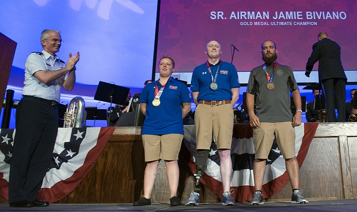 Air Force Gen. Paul J. Selva, vice chairman of the Joint Chiefs of Staff, applauds ultimate champion medal recipients, from left, Air Force Senior Airman Jamie Biviano, gold; Air Force Capt. Austin Williamson, silver; and Marine Corps Staff. Sgt. John Stanz, bronze, during the closing ceremony for the 2017 Department of Defense Warrior Games in Chicago, July 8, 2017. (DoD photo by EJ Hersom)