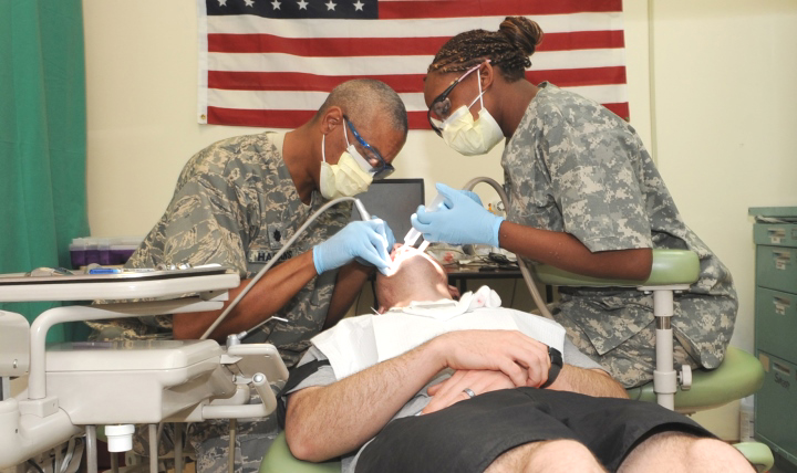 Air Force Lt. Col. Val Hagans and Army Spc. Laketa Bryant extract a patient's wisdom teeth at Kirkuk Regional Air Base, Iraq in 2010. (Photo by Air Force Staff Sgt. Tabitha Kuykendall)