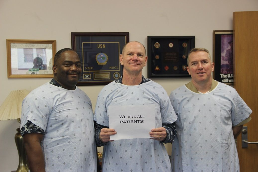 Three U.S. Naval Hospital Naples commanders wear patient safety gowns in honor of Patient Safety Awareness Week.