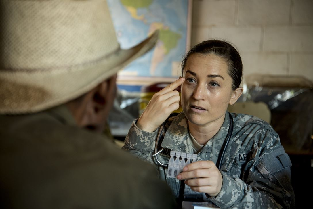 A U.S. Army nurse explains how to use eye drops to a patient during a medical readiness training exercise.