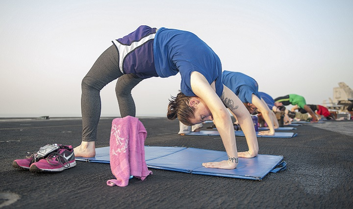 Navy Petty Officer 3rd Class Tara Paradiso participates in a sunrise yoga class on the flight deck aboard the aircraft carrier USS Theodore Roosevelt. If you're thinking of adding exercise to your pain management plan, consider the following types: aerobic, strength, and flexibility. But make sure your exercise program is specifically tailored to your needs. Some exercises might be easier or more difficult to complete depending upon the type and location of your pain. (U.S. Navy photo by Mass Communication Specialist 2nd Class Chris Liaghat)