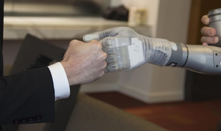 "Dr. Justin Sanchez, director of the Defense Advanced Research Projects Agency's Biological Technologies Office, fist-bumps with one of the first two advanced ""LUKE"" arms to be delivered from a new production line during a ceremony at Walter Reed National Military Medical Center in Bethesda, Maryland."