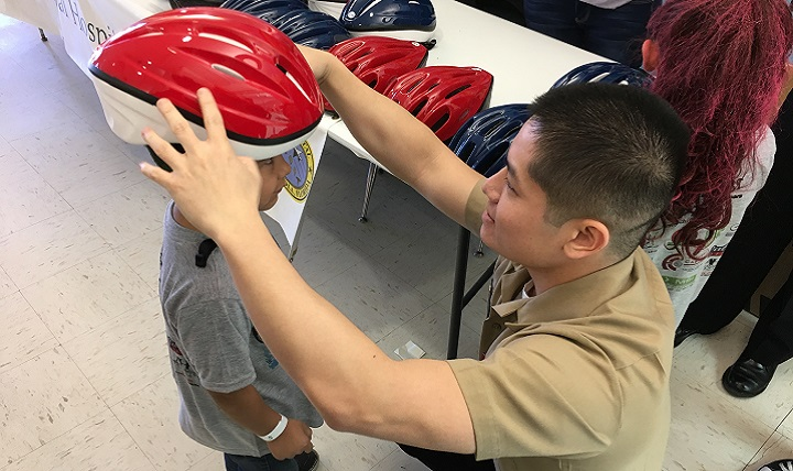 Navy Hospital Corpsman 3rd Class Thien Trinh, a corpsman with Naval Hospital Pensacola's Neurology Department, places a helmet on Knight Moore, 5, to check if it fits properly. Sailors from Naval Hospital Pensacola's Neurology Department visited a local elementary school in Pensacola, Florida to promote helmet safety. (U.S. Navy photo by Jason Bortz)