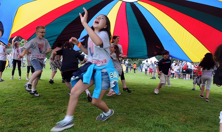 Children play parachute during a fitness-themed event. The festivities were part of a campaign to combat childhood obesity. (U.S. Air Force photo by Staff Sgt. Austin May)