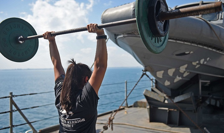 Damage Controlman 2nd Class Evelyn Medina lifts weights during a workout session on the boat deck of the amphibious dock landing ship USS Ashland.