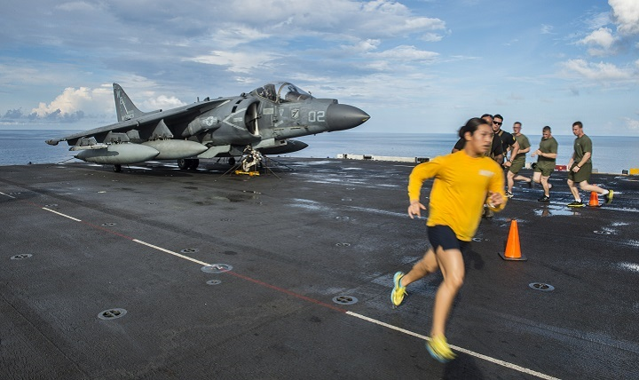 Sailors, along with embarked Marines from the 31st Marine Expeditionary Unit assigned to the forward-deployed amphibious assault ship USS Bonhomme Richard, run on the ship's flight deck.