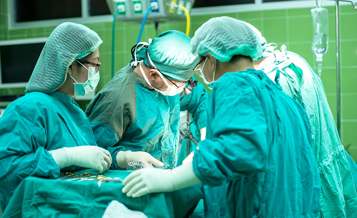 A group of four medical professionals wearing scrubs stand around a patient, performing a procedure in the operating room.